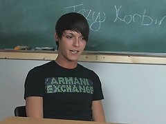 Lovely young twink pornstar Trey Korbin is sitting at a desk wearing a t-shirt and lo